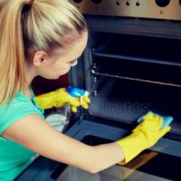 depositphotos_99542246-stock-photo-happy-woman-cleaning-cooker-at